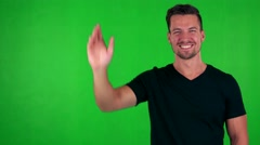 Young handsome caucasian man waves with hand - green screen - studio Stock Footage
