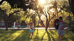 Happy girl and boy playing at park with swing Stock Footage