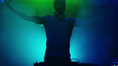 Backlit DJ Playing Music in Nightclub. Silhouette of a DJ. Stock Footage