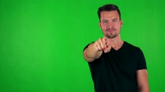 Young handsome caucasian man points to camera with finger - green screen  Stock Footage