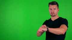 Young handsome caucasian man points on watch (show time) - green screen - studio Stock Footage