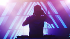 Backlit DJ Playing Music in Nightclub. Silhouette of a DJ Stock Footage