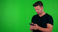 Young handsome caucasian man works (typing) on smartphone - green screen  Stock Footage
