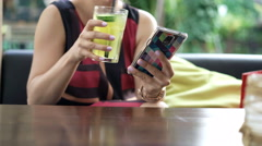 Woman using smartphone and drinking beverage in cafe in garden Stock Footage