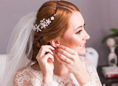 Bride takes the earrings close-up, wedding preparation Stock Photos