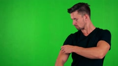 Young handsome caucasian man adjusts clothes and smiles to camera - green screen Stock Footage