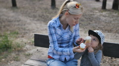 Happy mother and little daughter eating ice cream on the bench Stock Footage