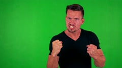 Young handsome caucasian man is angry to camera - green screen - studio Stock Footage