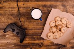 Gamepad and homemade chocolate chip cookies on rustic wooden tab Stock Photos
