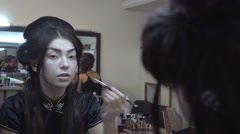Beautiful brunette Asian Girl puts on Face make-up Cosmetics before a Mirror Stock Footage