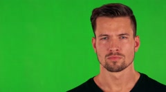 Young handsome caucasian man looks to camera with serious face - green screen  Stock Footage