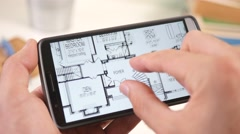 4K Looking at a House Plan Blueprint on Smartphone Touchscreen Stock Footage