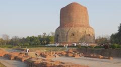 Pilgrims carrying long buddhist cloth around Dhamekh Stupa,Sarnath,India Stock Footage