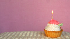 Birthday cupcake with burning candle on pink background with copy space Stock Footage