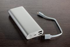 Silver aluminum power banks - dark wooden background Stock Photos