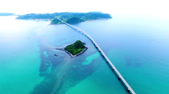 Aerial shot of bridge spanning blue ocean Stock Footage