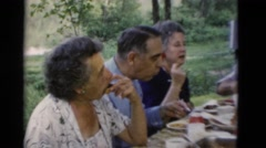 1949: group of older people having a meal and talking outdoors around a table Stock Footage