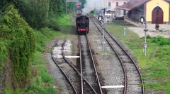 Old steam train and antique carriages run on the tracks between rice fields Stock Footage
