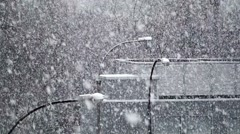 Snow Storm in the City against the backdrop of Street Lamps and Buildings Stock Footage