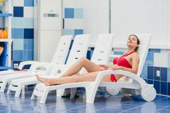 Body care. Woman with perfect body in red bikini lying on the deckchair by Stock Photos