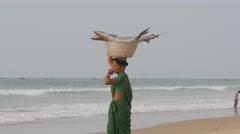 Woman carrying big fish in basket on head,Puri,India Stock Footage