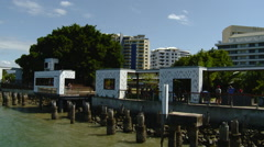Cairns Australia - Logs in Harbor with BBQ Huts on Harbor Promenade Stock Footage