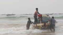 Men pushing boat in waves of sea,Puri,India Stock Footage