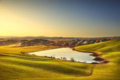 Tuscany, Crete Senesi rural landscape on sunset, Italy. Lake and green fields Stock Photos