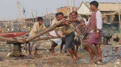 Men pulling boat on beach with pulley,Puri,India Stock Footage