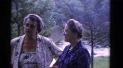 1949: four senior citizens enjoying conversation and cocktails by the lake Stock Footage