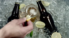 4k Shot of Cold Ice With Beer and hand Dropping Lemon in Glass Stock Footage