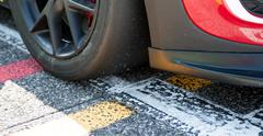 Racing car tire detail on asphalt starting line Stock Photos