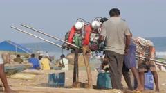 Fishermen preparing engine of boat,Konark,India Stock Footage