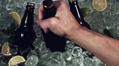 4k Shot of Cold Ice Cubes and Hand putting a Beer Bottle Stock Footage