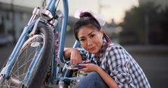 Chinese woman giving her bicycle a quick tuneup Stock Photos