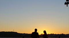 Romantic couple at sunset on bright orange sky background, love tenderness Stock Footage