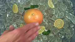 4k Shot of Cold Ice Cubes and Hand Places Orange Stock Footage