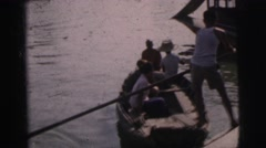 1962: man navigating a small wooden boat through the water  Stock Footage
