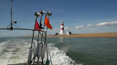 Fishing Vessel at sea sailing past Orford Ness Lighthouse Stock Footage