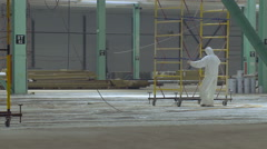 Person in White Cloths Moving a Wheeled Painting Platform Around the Hangar Stock Footage