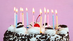 Birthday cake with candles on pink background Stock Footage