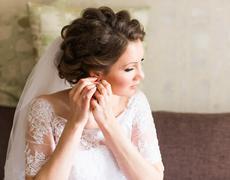 Bride takes the earrings, wedding preparation Stock Photos