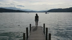 Pensive woman stands on dock of clear lake Stock Footage