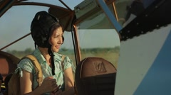 Woman pilot in old airplane at sunset Stock Footage