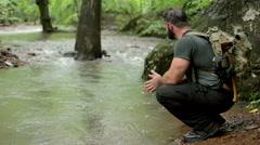 Hiker Rests Beside Flowing Creek Stock Footage
