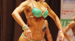 Tanned female demonstrating relaxed pose at bodybuilding contest, ideal body Stock Footage