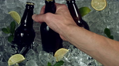 4k Shot of Cold Ice Cubes and Hand Taking Beer Bottle Stock Footage