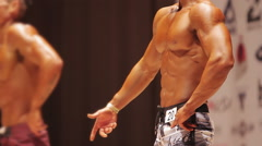Strong men in shorts standing on stage at bodybuilding contest, perfect body Stock Footage