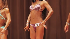 Thin female standing on stage in front lat spread pose at bodybuilding contest Stock Footage
