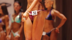 Pretty girl in bikini leaving stage, bodybuilding contest, professional sport Stock Footage